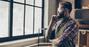 successful handsome cabinetmaker look to the side at window. Stylish young entrepreneur with brutal hairstyle and glasses holding chin and dream at his workstation