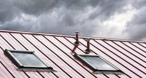 new grey metal roof with skylights against blue sky